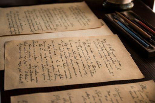 Imagen en la que se ve documentos de archivos puestos encima de la mesas de un archivo